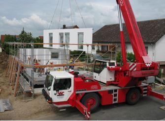 Abbildung 2: Dieses Baustellenbild zeigt, wie eine fertige Hausmauer samt Fenster gebracht und eingesetzt wird. Dieses Bild ist typisch für die Fertigbauweise.